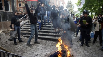 Pro-Russian activists burn uniforms outside the prosecutor's office in Donetsk